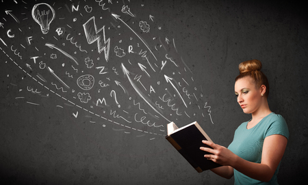 Young woman reading a book while hand drawn sketches coming out of the book photo