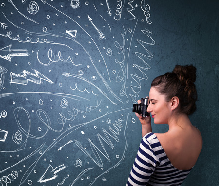 Photographer girl shooting images while energetic hand drawn lines and doodles come out of the camera photo