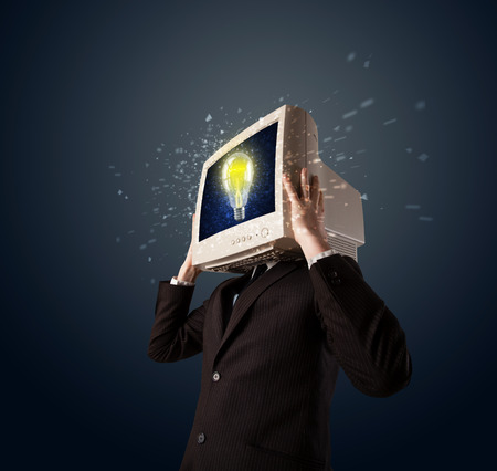 Business man with a pc monitor head and idea light bulb glowing in the display photo