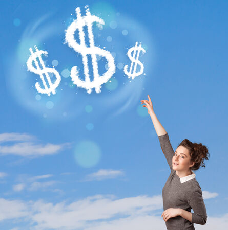 Young girl pointing at dollar sign clouds on blue sky concept photo