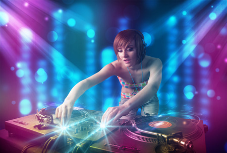 Pretty Dj mixing music in a club with blue and purple lights photo