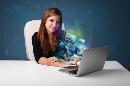 Beautiful young girl sitting at desk and watching her photo gallery on laptop photo