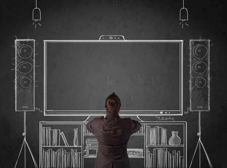 Young businessman standing and enjoying home cinema system sketched on a chalkboard photo