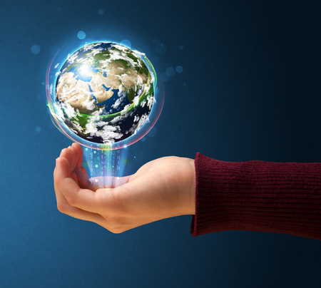 Young woman holding in her hand a glowing earth globe photo
