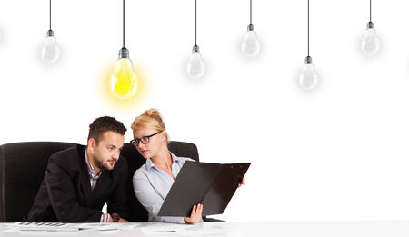 Business man and woman sitting at table with bright idea light bulbs photo