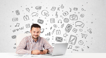 Good-looking young businessman with all kind of hand-drawn media icons in background photo