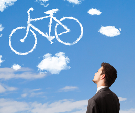 Young business man looking at bicycle clouds on blue sky photo