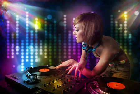 Pretty Dj girl playing songs in a disco with light show photo