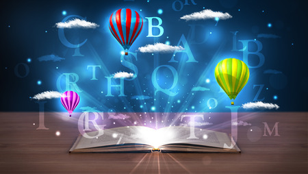 Open book with glowing fantasy abstract clouds and balloons on wood deck photo