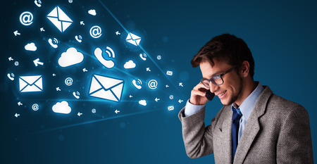 Young man staning and making phone call with message icons photo