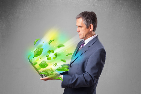 Handsome businessman holding laptop with recycle and environmental symbols photo