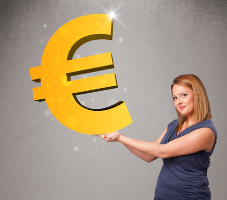 Beautiful young girl holding a big 3d gold euro sign photo