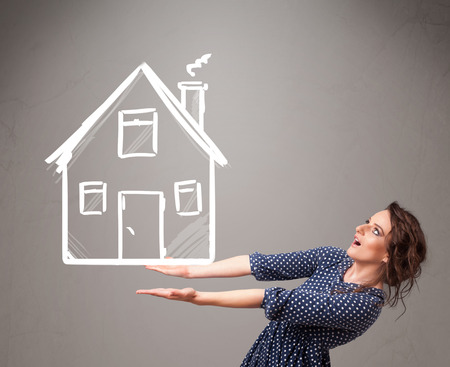 Beautiful young lady holding a huge drawn house photo