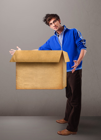 Goog-looking young man holding an empty brown cardboard box photo