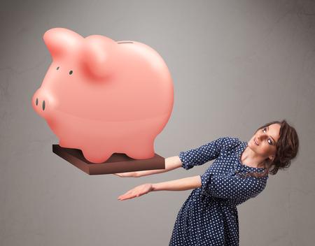 Beautiful young girl holding a huge savings piggy bank photo