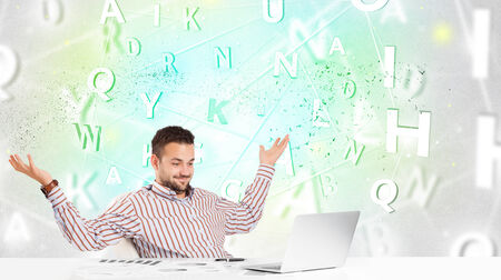 Business man at white desk with green word cloud photo