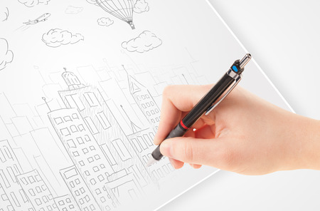 A person drawing sketch of a city with balloons and clouds on a plain paper  photo