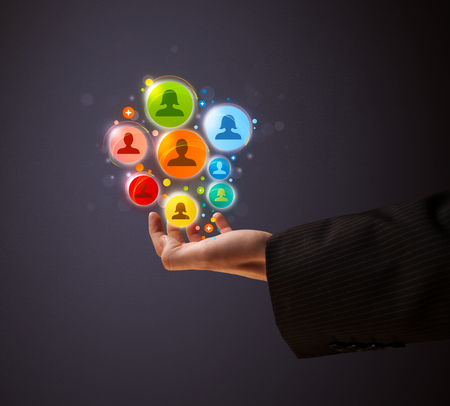 Businessman holding colorful social network icons in his hand photo