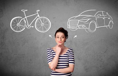 Mooie jonge vrouw het nemen van een beslissing tussen fiets en auto Stockfoto