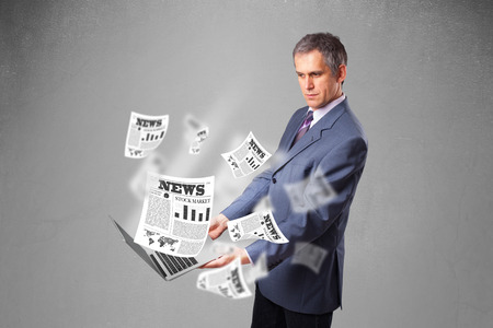 Handsome middle aged businessman holding notebook and reading the explosive newspaper photo