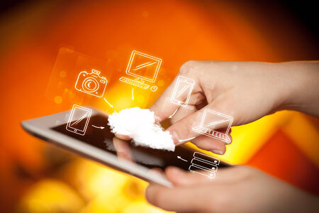 tablet pc in hand: Hand touching tablet pc, mobile cloud concept