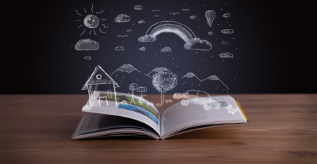 Open book with hand drawn landscape on wooden deck photo