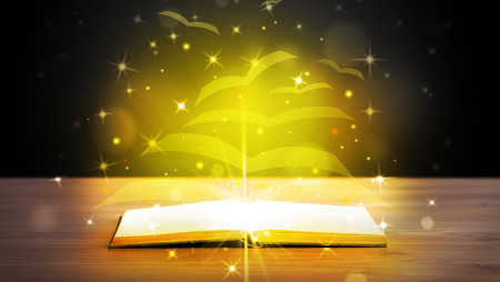 Open book with golden glow flying paper pages on wooden deck photo