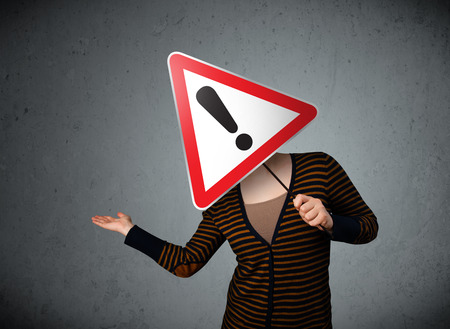 Young woman holding a red traffic triangle warning sign in front of her head photo