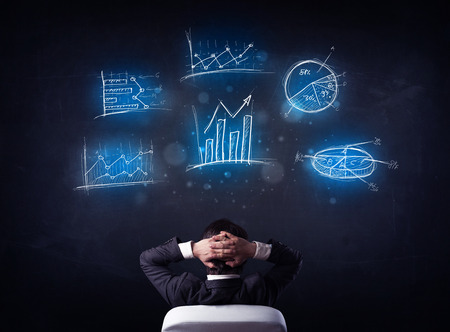 Young businessman sitting in office chair with glowing charts above his head photo