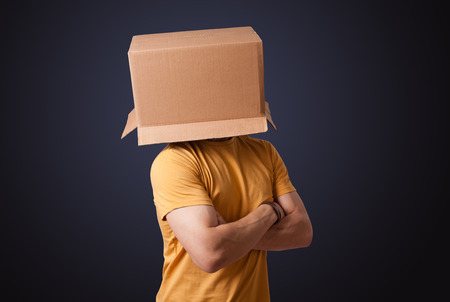 boxy: Young man standing and gesturing with a cardboard box on his head