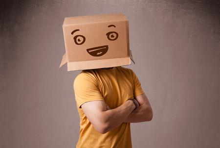 emotions faces: Young man standing and gesturing with a cardboard box on his head with smiley face