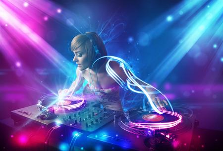 Energieke DJ meisje het mengen van muziek met krachtige lichteffecten