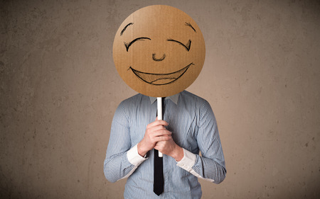 male face: Businessman holding a cardboard smiley face emoticon in front of his head Stock Photo