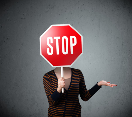 direction sign: Young lady standing and holding a stop sign in front of her head