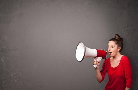 hablar en publico: Muchacha bonita que grita en el meg�fono en el espacio de la copia de fondo