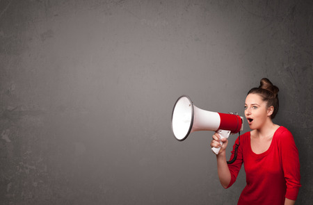 public speaking: Pretty girl shouting into megaphone on copy space background