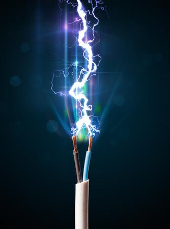 redes electricas: Cable el�ctrico de primer plano con un rayo de electricidad que brilla intensamente