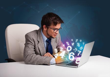 teclado numerico: Hombre joven y guapo sentado en el escritorio y escribiendo en la computadora portátil con los números 3d comming fuera