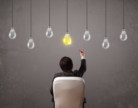 businness: Businness guy in front of bright idea light bulbs concept Stock Photo