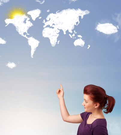 Young casual girl looking at world clouds and sun on blue sky photo