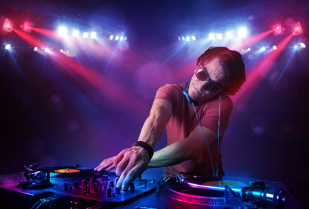 audio mixer: Handsome teenager dj mixing records in front of a crowd on stage
