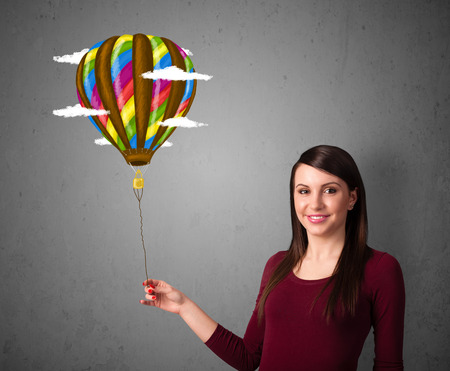 Young woman holding a balloon drawing with clouds photo