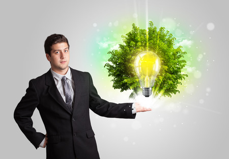 Young man presenting idea light bulb with green tree concept photo