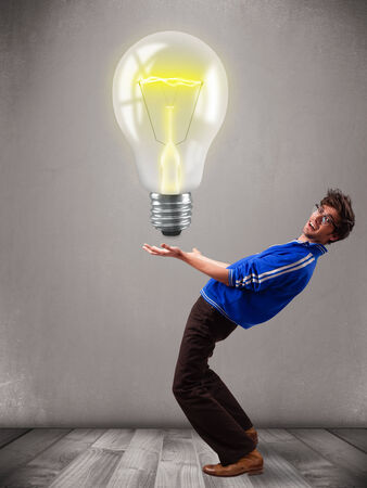 Attractive young man holding realistic 3d light bulb photo