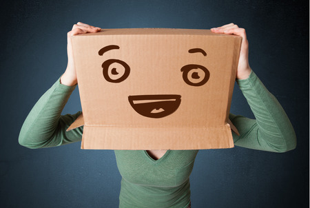 Young woman standing and gesturing with a cardboard box on her head with smiley face photo