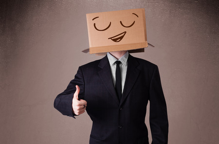 Businessman standing and gesturing with a cardboard box on his head with smiley face photo