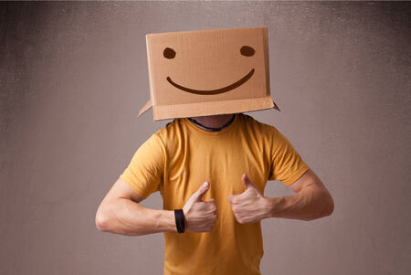 male face: Young man standing and gesturing with a cardboard box on his head with smiley face