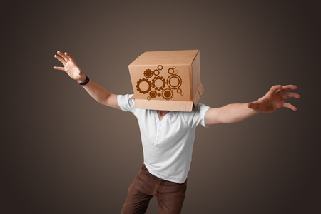 Young man standing and gesturing with a cardboard box on his head with spur wheels photo