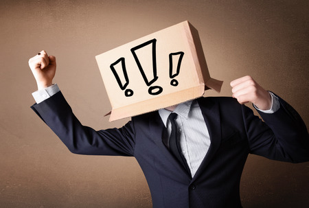 boxy: Businessman standing and gesturing with a cardboard box on his head with exclamation point Stock Photo