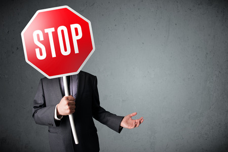 warning signs: Businessman standing and holding a stop sign in front of his head Stock Photo
